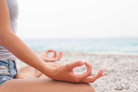gyan: Young woman relaxing by practicing yoga on the beach, close-up of hands, gyan mudra and lotus position