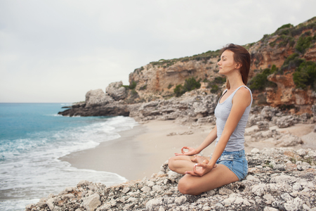 Woman doing yoga on the sea background