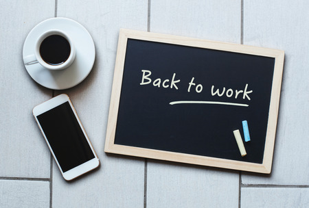 Chalkboard or Blackboard concept saying Back to Work with coffee and mobile phone. The concept education, training, after vacation, maternity leave, break