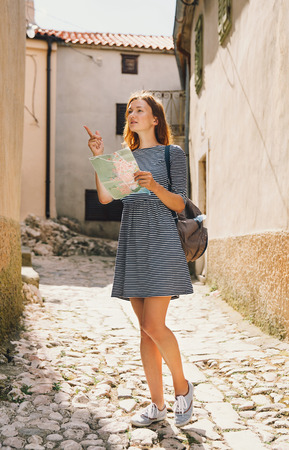 krk: Young woman with a map indicating the side on the background of the old European streets. Krk Island, Croatia Stock Photo