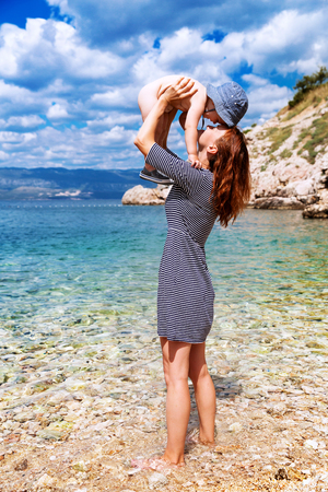 krk: Young beautiful mother and her adorable son having fun on the beach. Happy family relaxing by the sea. Croatia, island Krk.