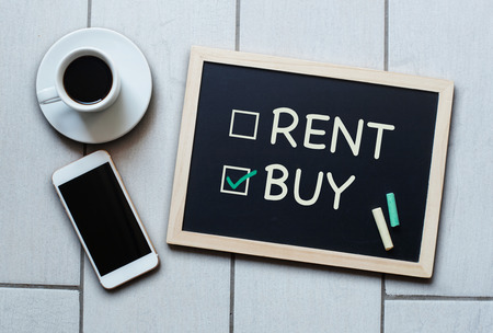 Buy not rent blackboard concept. Choosing buying over renting with coffee and mobile phone