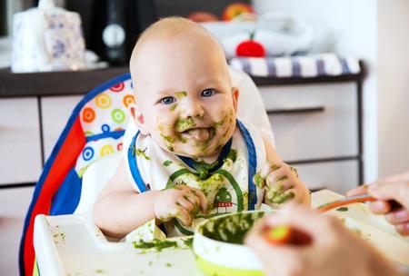 Alimentation. Adorable bébé enfant de manger avec une cuillère dans la chaise haute. premier aliment solide de Bébé. Affichage de la langue, les taquineries. Regardant l'objectif Banque d'images - 61662618