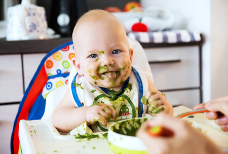 Feeding. Adorable baby child eating with a spoon in high chair. Babys first solid food. Showing tongue, teasing. Looking at camera