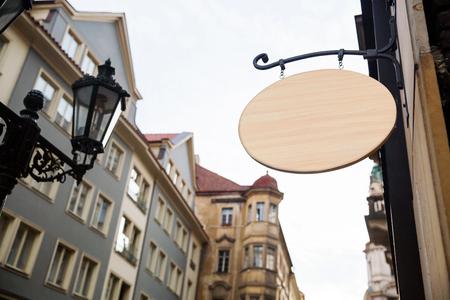 ヨーロッパの街並みに空の木製看板。テキストの準備完了をクローズ アップ建築ディテール