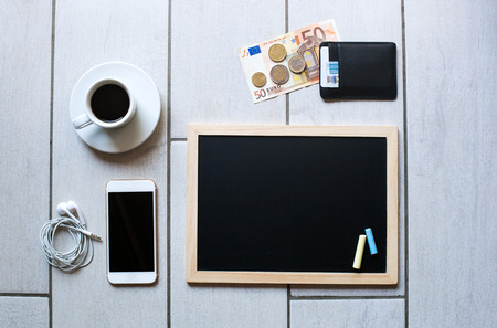 employment elementary school: Chalkboard or Blackboard ready for text. Education or working, business, job concept. Stylish office background with coffee, wallet with euro money, mobile phone and headphones.