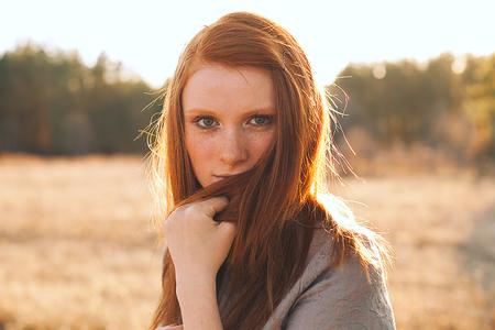 Portret van Beauty Teenage Model meisje met rood haar op de achtergrond van de natuur op het veld in Sun Light. Gezicht van de jonge vrouw met sproeten. Herfst. Glow Zon, Sunshine. Backlit. Warme kleuren