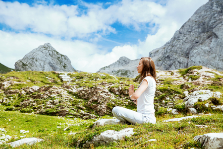 Woman doing yoga and meditating in lotus position on the background of sky and mountains. Mangart, Julian Alps, National Park, Slovenia, Europe. Concept of Meditation, Relaxation and Healthy Life.