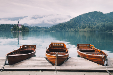 karavanke: Traditional wooden boats on the backgorund of Church on the Island on Lake Bled, Slovenia. Amazing View On Bled Lake. Autumn time in Slovenia, Europe.
