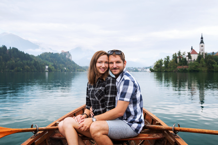 karavanke: Young couple of tourists in love on traditional wooden boat on the Lake Bled, Slovenia. Background with Bled Castle and Church on the Island on Lake Bled. Autumn time in Europe.