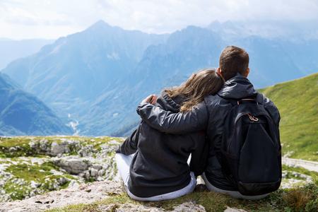 Paar van de reizigers (wandelaars) op de top van een berg te genieten van uitzicht op de vallei. Mangart is een berg in de Julische Alpen, gelegen tussen Italië en Slovenië. Reizen, vakantie, vrijheid en Lifestyle Concept Stockfoto