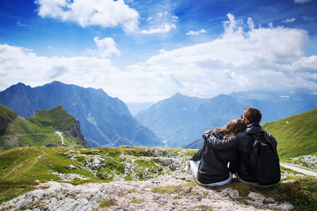 julian: Couple of travelers (hikers) on top of a mountain enjoying valley view. Mangart is a mountain in the Julian Alps, located between Italy and Slovenia. Travel, Holidays, Freedom and Lifestyle Concept Stock Photo