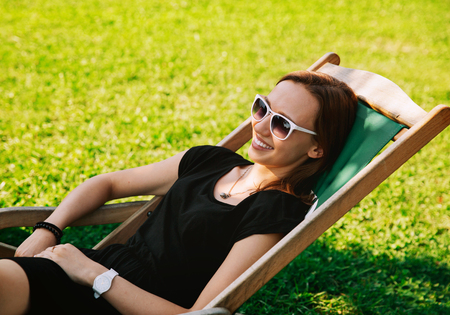 Happy Young Woman Relaxing Outdoor on the Background with Green Grass. Park or Outdoor Cafe. Studing, Communicate, Holidays, Vacation, Love and Friendship Concept. Stock Photo