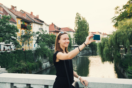 old center: Beautiful young woman making selfie photo on mobile phone camera in old center of Ljubljana, Slovenia. Smiling tourist on the background of Ljubljana cityscape with river and houses at sunset.