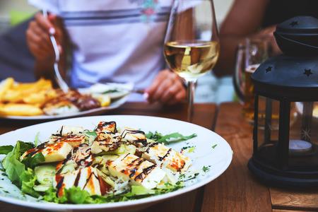 Diner in het restaurant. Close-up salade met gegrilde kaas. Mensen eten op de achtergrond Stockfoto
