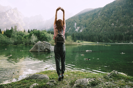 Traveler with raised arms up on the nature with Lago di Fusine lake with Mangart mountains in the background. Travel, Freedom, Lifestyle concept. Udine, Italy, Europe.