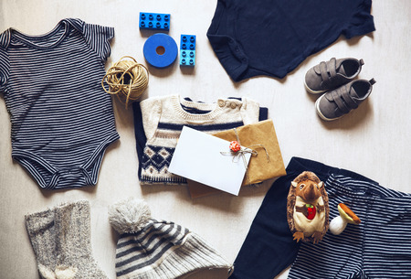 stuff toy: Autumn or winter childrens outfit clothes. Top view fashion trendy look of baby clothes with greeting card with cutest newborn baby  and accessories for the fall or winter.