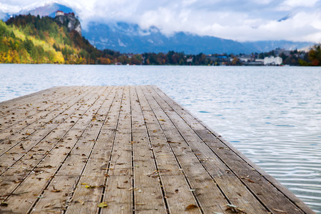 karavanke: Wooden Pier on the Alpine Lake Bled. Autumn in Slovenia, Europe. View on Island with Catholic Church in Bled Lake with Castle and Mountains in Background. Stock Photo