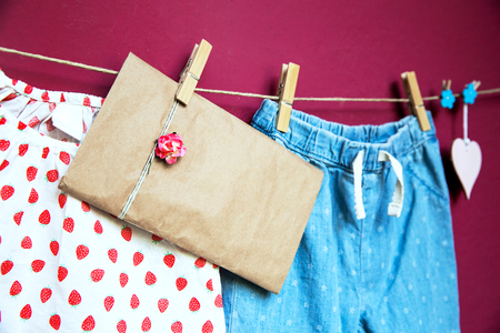 baby stuff: Baby child clothes and goods, blank note or greeting card hanging on clothespins on the clothesline on a textured wall background with copy space. Baby concept background.