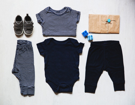 Baby clothes, concept of child fashion. Flat lay childrens clothing and accessories. Baby template background with copy space. Top view fashion trendy look of baby clothes and toy stuff. Stock Photo