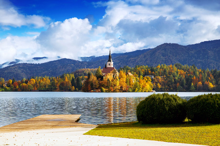 karavanke: Amazing View On Bled Lake. Autumn in Slovenia, Europe. View on Island with Catholic Church in Bled Lake with Autumn Forest and Mountains in Background.