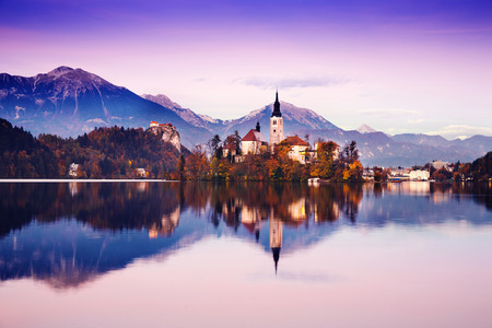 Amazing View On Bled Lake. Autumn in Slovenia, Europe. View on Island with Catholic Church in Bled Lake with Castle and Mountains in Background.