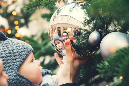 The first Christmas and New Year! Cute baby looking at a reflection in a bowl on a Christmas tree. Holidays, Christmas, Family concept. Mother and son at winter outdoor among Christmas decorations