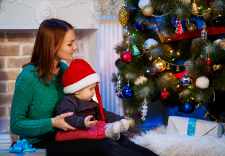 stuff toy: Happy family at a home interior on background of the Christmas tree with gifts. Beautiful mother and little cute baby among Christmas decorations.
