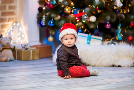 stuff toy: Cute little baby child boy in Santa red hat sitting at a home interior on background of the Christmas tree with gifts.
