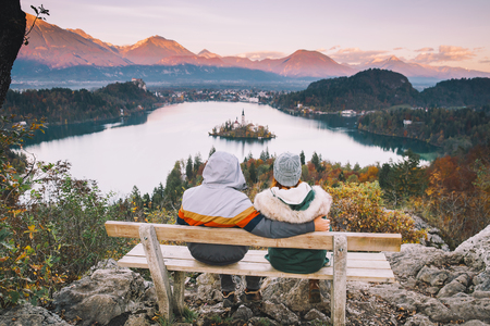 karavanke: Lovers travel Europe. Couple in love looking on Bled Lake. Autumn or Winter in Slovenia, Europe. Top view on Island with Catholic Church in Bled Lake with Castle and Mountains in Background. Stock Photo
