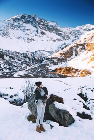 rauris: Family of travelers walking in winter snowy countryside with mountain on the background. Winter mountain hike in Austria. Active healthy mother with her baby in carrier.