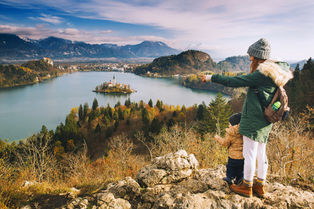 Family travel Europe. Mother with son looking on Bled Lake. Autumn or Winter in Slovenia, Europe.