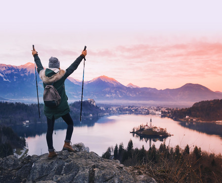 Travel Slovenia, Europe. Woman looking on Bled Lake with Island and Alps Mountain on background. Top view. Bled Lake one of most amazing tourist attractions. Sunset winter nature landscape. Archivio Fotografico
