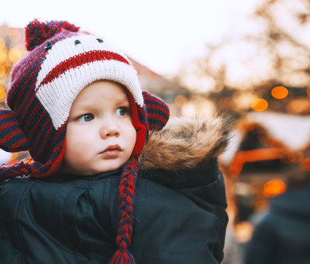 Portrait of child in a funny hat spend winter holidays with family in the old town of Klagenfurt, Austria. Holidays, Christmas, Family concept. Child at winter outdoor among Christmas decorations