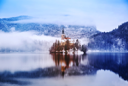 Winter landscape Bled Lake. Travel Slovenia, Europe. Bled Lake one of most amazing tourist attractions. View on snowy Island with Catholic Church in Bled Lake.