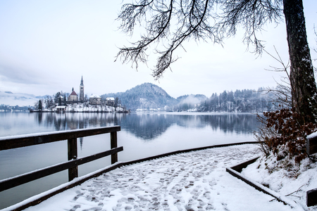 Snowy wooden Pier on the Alpine Lake Bled. Winter landscape. Travel Slovenia, Europe. Bled Lake one of most amazing tourist attractions. View on snowy Island with Catholic Church.