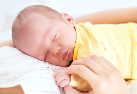 Newborn sleeping child in the hands of mother Stock Photo - 71376324