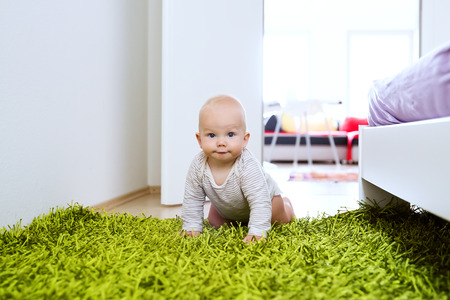 explores: Portrait of charming 8-9 month old baby child at home interior. Curious, smiling child explores the world around. Cute crawling child Stock Photo