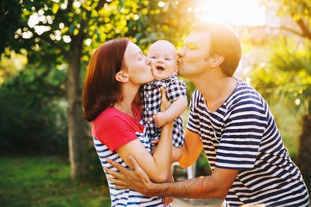 Gelukkig gezin met plezier en lachen op een lente zomerse dag bij zonsondergang. Moeder, vader en schattige kleine baby Child at stijlvolle casual kleding op de natuur. Ouders en de activiteit met baby buitenshuis.