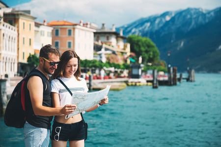 Travel Italy, Europe. Smiling couple in love with a map at Lake Garda with mountains, lake and town on the background. Lake Garda is the largest lake in Italy. Lifestyle, Holidays and Travel Concept. Reklamní fotografie