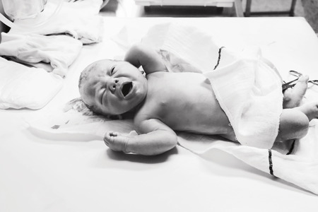 Newborn in nursery after childbirth. Newborn baby in delivery room. Nurse or doctor examining a newborn baby. Black and white photo.