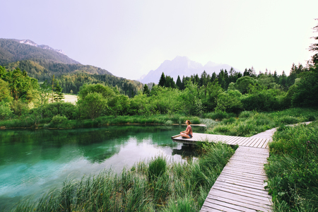 Young woman doing yoga and meditating in lotus position on the background of nature. Concept of Meditation, Relaxation and Healthy Life. Slovenia, Europe.