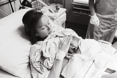 Mother holding her newborn baby child after labor in a hospital. Black and white photo. Parent and infant first moments of bonding.