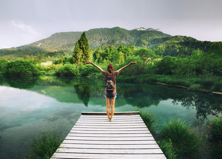 Young woman stands on a wooden bridge with raised arms up on the nature background. Travel, Freedom, Lifestyle concept. Slovenia, Europe. Archivio Fotografico