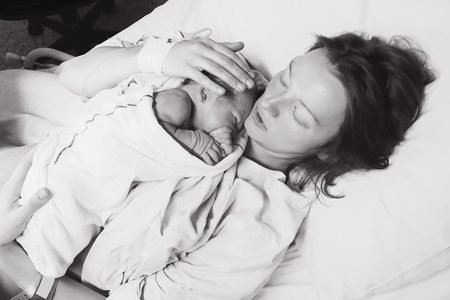 Mother holding her newborn baby child after labor in a hospital. Mother giving birth to a baby boy. Black and white photo. Standard-Bild