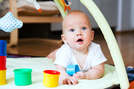 teething: Baby playing with colorful toys at home. Happy 6 months old baby child playing and discovery.
