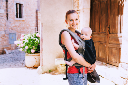 Beautiful young mother with baby child in carrier in the old town of Pula, Croatia. Travel family of tourists on the background of the European street. Active travel family vacation