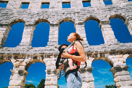 Beautiful young mother with baby child in carrier in the old town of Pula, Croatia. Travel tourist tour of the popular historical attractions of Istria County. Active travel family vacation
