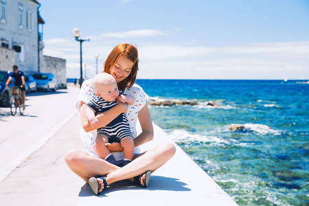 Smiling mother with cute baby child son having fun on the coast near sea beach. Happy family relaxing by the sea. Coast of Croatia
