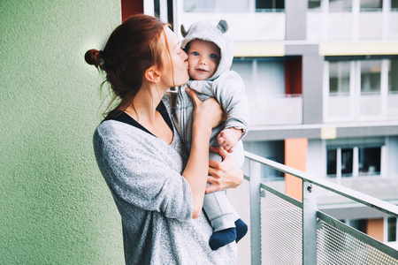 Portrait of a fashionable cute baby child in a hoodie romper. Mom and her son outdoors.